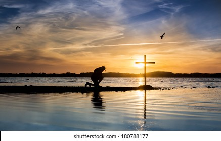 Cross at a lake with a man in prayer beside it, as the sun goes down.