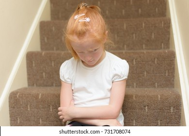 Cross little girl sitting on the naughty step.