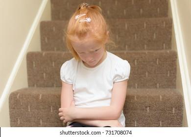 Cross little girl sitting on the naughty step.