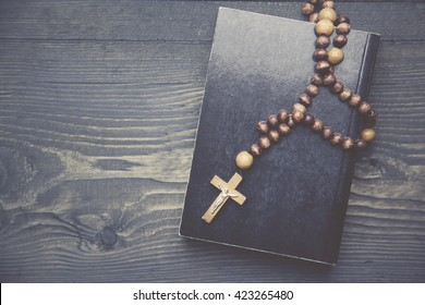 cross on book on wooden table