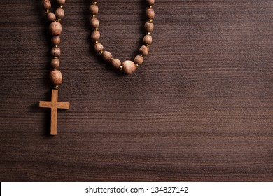 cross on the brown wooden table background