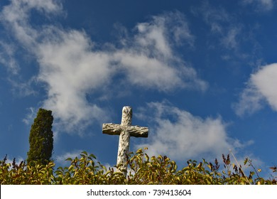 Cross on a cemetery in among green bushes in sunny day. Blue sky