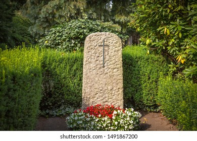 Cross on a gravestone with red and white flowers