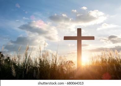 The cross on green grass with sunset in the sky background