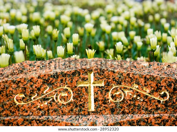 A Cross on headstone with yellow flowers