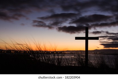 Cross on a hill over looking a river town at dawn.