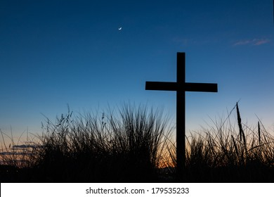 Cross on a hill with tusket grass around it, at a start of a new day.