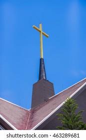 Cross on public church roof on blue sky in Thailand