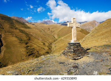 Cross on a pyramid of stones on Kazbek Mount Background near Gergeti Trinity Church in Georgia. Autumn Or Summer Season.
