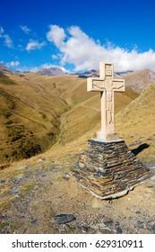Cross on a pyramid of stones on Kazbek Mount Background near Gergeti Trinity Church in Georgia. Autumn Or Summer Season.