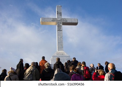 The cross on the top of Mount Krizevac in Medjugorje, Bosnia and Herzegovina on 2016/11/11. Many unidentified pilgrims reaching the top.