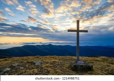 Cross on the top of a mountain with beautiful sky. Symbol of christianity