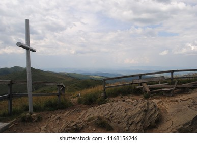 Cross on the top of the peak in the Bieszczady mountains. Halicz mountain in the summer. Beautiful landscape after hiking. Clouds and grass in the background. View, scape, scenery.