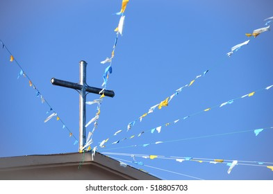 Cross on top of a roof with colorful flaglets