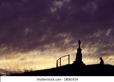 Cross with a person against the sky