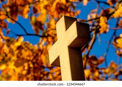cross of a pilgrim way with autumnal painted leaves