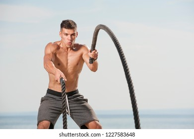 Cross power training. Close-up Young shirtless muscular man training with battle ropes on the beach against blue sky. Place for text.