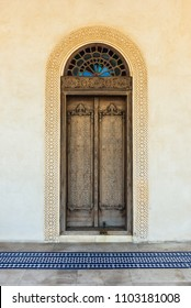 A cross process filtered view of an elaborately carved exterior door with a glass arch and a carved gypsum surround stands in front of a patterned, tiled floor in a restored traditional arabian house.