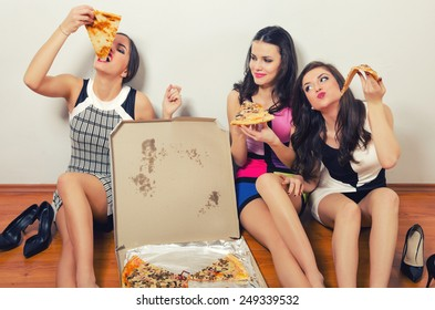 Cross processed image of three beautiful young ladies eating pizza while sitting on the floor.