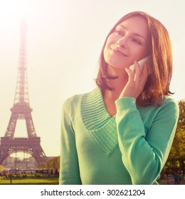 cross processed picture. France with Eiffel Tower in background. Cute beautiful Caucasian female model holding a phone in her hand and sliling.