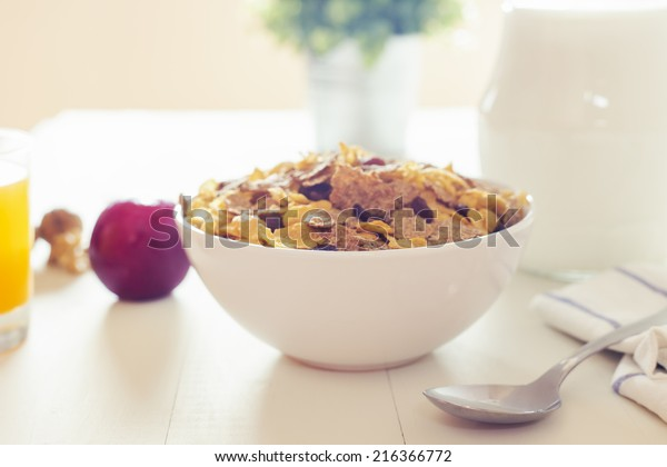 Cross processing style for a delicious breakfast on a white wood table with a belly pitcher of milk, a bowl with cornflakes and raisins, orange juice and opened walnuts.