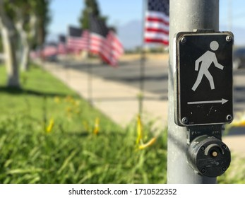Cross road sign on the street with american flags as background in Chio hills, California, USA. May 1, 2017.