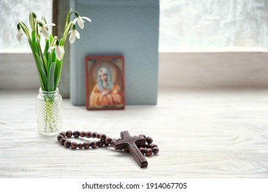 cross, rosary beads, flowers, orthodox icon of Holy Virgin Mary and bible books. concept of faith, God, orthodox Church Holiday, lent.