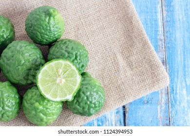 Cross section bergamot or bergamot slice.Close up bergamot on wooden table background. with some juice,popular ingredient for Thai cuisine, also for hair shampoo or conditioner treatment. Kaffir lime