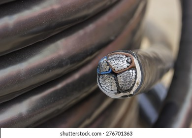 Cross section of electric black industrial underground cable on large wooden reel. Four core al cable. Selective focus and shallow dof.