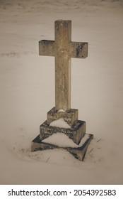 Traversez la vieille pierre tombale d'un cimetière couvert de neige en hiver. Image mystérieuse, effrayante et gothique.