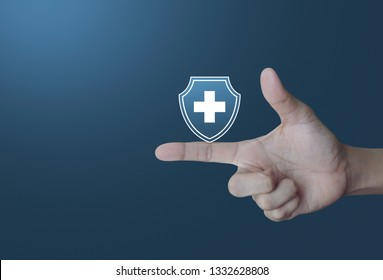 Cross shape with shield flat icon on finger over light gradient blue tone background, Business healthy and medical care insurance concept