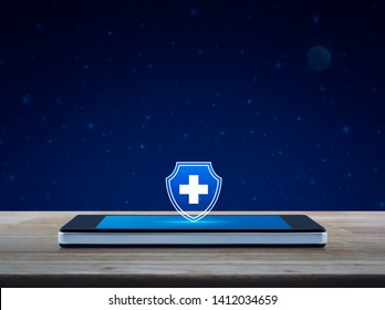Cross shape with shield flat icon on modern smart mobile phone screen on wooden table over fantasy night sky and moon, Business healthy and medical care insurance online concept
