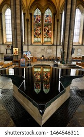 Cross shaped Baptismal Font fountain reflecting stained glass window of Jesus with children inside the medieval Salisbury Cathedral Salisbury, England - June 10, 2019