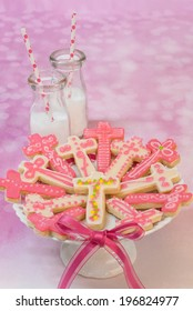 (cross shaped) pink cookies on small cake stand with milk bottles and straws
