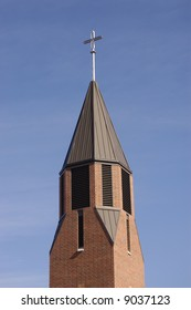 A cross shines at the top of a church bell tower