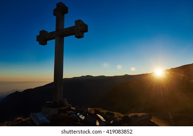cross sign on the mountain peak pass at sunset