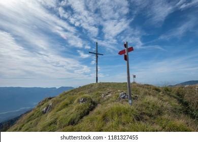 Cross and sign post on the top of mountain Veliki Rogatec in Kamnik-Savinja Alps, Slovenia