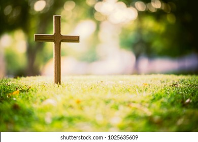 The cross standing on meadow sunset and bokeh background.Cross on a hill as the morning sun comes up for the day.The cross symbol for Jesus christ.Christianity, religious, faith, Jesus or belief.