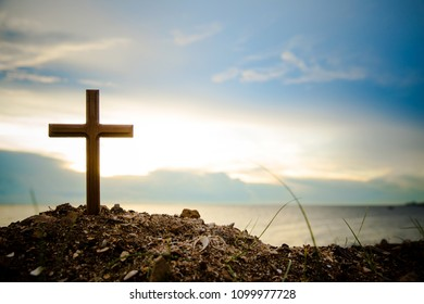 The cross standing on meadow sunset and flare background.Cross on a hill as the morning sun comes up for the day.The cross symbol for Jesus christ.Christianity, religious, faith, Jesus or belief.