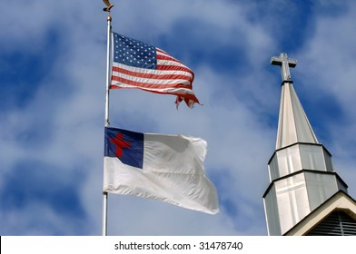 Cross stands tall besides an American flag and a christian flag.  Blue skies and soft clouds fill background.