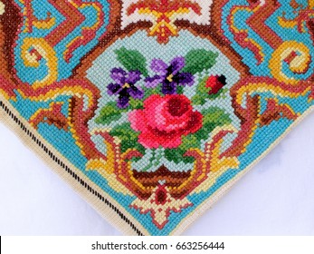 Cross Stitch Handmade Embroidery on a White Background. Embroidered cushion cover. Needlework. Floral pattern close-up. Reconstruction of ancient embroidery. Art and craft conception.