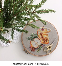 Cross stitch needlework process. Canvas in a wooden Hoop. Pattern Apple and hot tea.