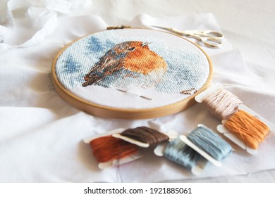 cross stitch process in the hoop multicolored bird, white canvas, floss threads on bobbins, needle, needlework and cross stitch concept