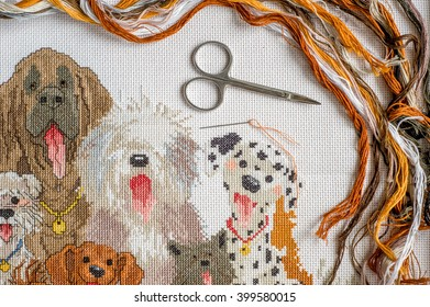 cross stitching on the canvas. Dogs during embroidery. Colored thread, scissors, a needle, a set for needlework.