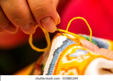 The cross stitching. Photo of woman hands closeup, which holds the needle and the embroidering. Selective focus 5