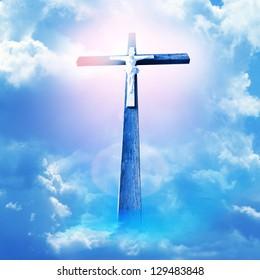 cross in sun rays against cloudy sky