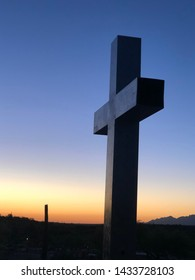 Cross and sunset with orange and blue sky. Taken in Arizona.