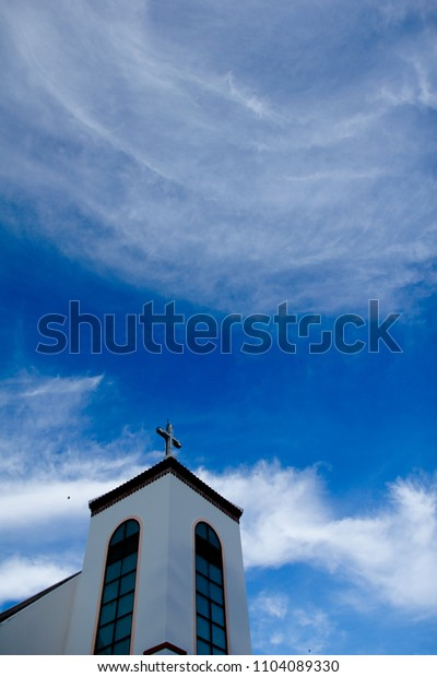 The cross at the top of the church Sky background