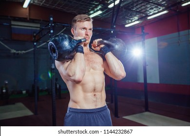 Cross training fit. Fitness man doing a weight training by lifting kettlebell. Young athlete doing kettlebell swings. Bodybuilder lifting kettlebell. Cross instructor fit at the gym. Cross in the gym