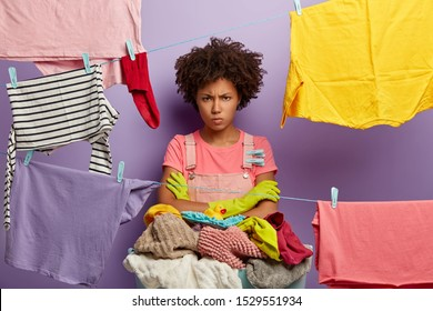 Cross unhappy housewife stands with arms folded, hands washed laundry, angry with much duties about house, uses clothespegs, isolated over violet wall. People, housework and washing concept.